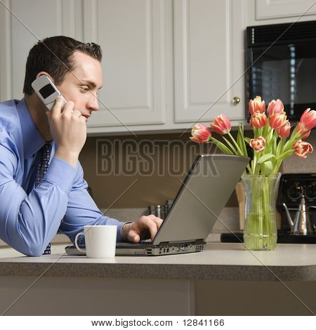 Caucasian man in suit using laptop computer and talking on cellphone in kitchen.