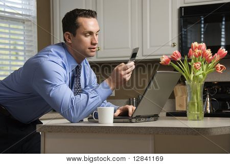 Caucasian man in suit using laptop computer and cellphone in kitchen.