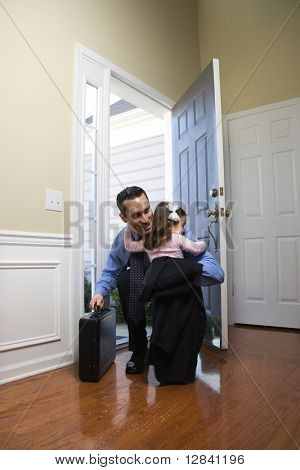 Caucasian businessman   at open door with briefcase hugging daughter.
