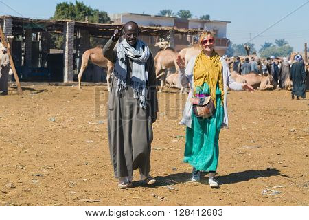 DARAW, EGYPT - FEBRUARY 6, 2016: Tourist with local man at Camel market.