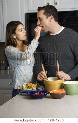 Caucasian woman feeding man at kitchen counter while he makes salad.