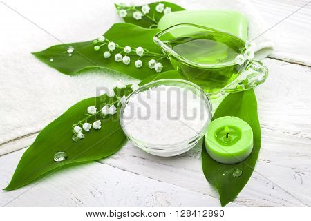 Spa still life of sea salt and essential oils and lily of the valley flowers