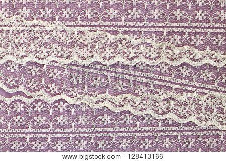 Lace textile ribbon on purple paper background