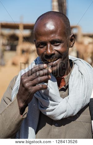 DARAW, EGYPT - FEBRUARY 6, 2016: Portrait of camel salesman drinking from glass at Camel market.