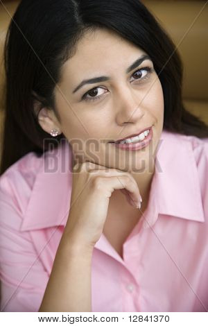 Mid adult Hispanic woman smiling at viewer with hand to head.