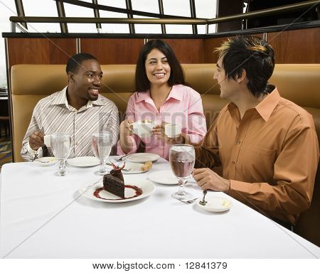 Small group of mid adult friends at restaurant talking and having dessert.