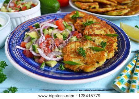 potato pancakes with vegetable salad on a blue background ** Note: Shallow depth of field