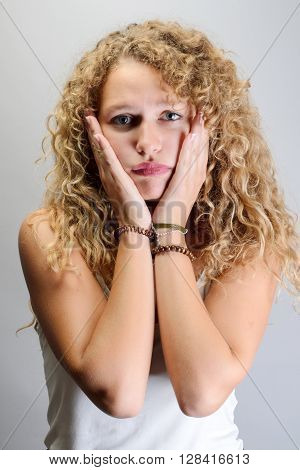 Attractive Young Woman With Curly Blond Hair  Holding Her Hands To Her Cheeks