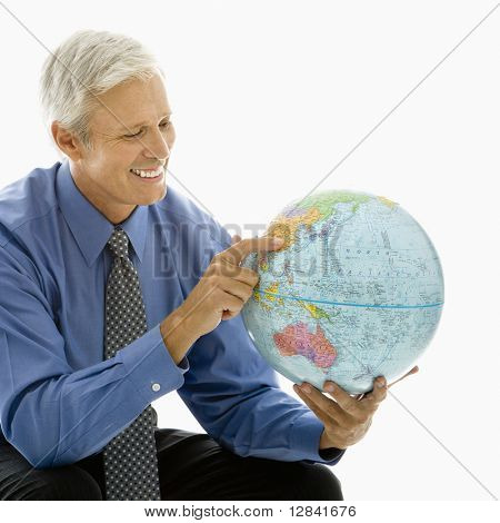 Middle aged Caucasian man pointing on globe.