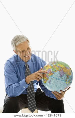 Middle aged Caucasian man holding globe and pointing.