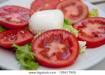Mozarella cheese with tomatoes sliced on a plate