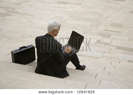 Back view of Caucasian middle aged businessman typing on laptop with briefcase sitting on steps outdoors.