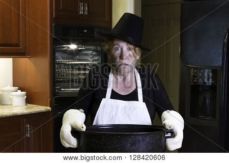 Woman standing in kitchen wearing pilgrim hat and apron with singed face and hair holding a roasting pan.