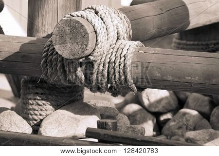of beige color a closeup fragment of a design from wooden logs is fastened by a rope
