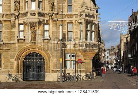 CAMBRIDGE, UK - DECEMBER 16: Pedestrians walk down Trinity Street, past Gonville and Caius College, Cambridge, UK on December 16, 2015.