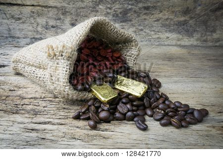Coffee beans and Gold Bullion in sackcloth bag on wooden background