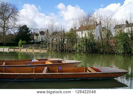 CAMBRIDGE, UK - FEBRUARY 23: Punts float along the bank of the River Cam in Cambridge, England on February 23, 2016, against a backdrop of winter trees and whitewashed period houses.