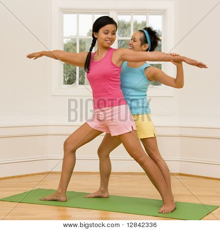 Young woman helping another young woman with positioning on her yoga pose.