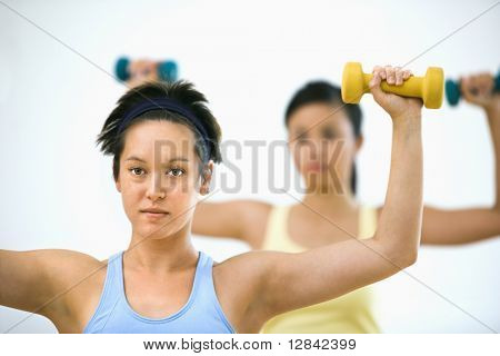 Young women at gym lifting hand weights.