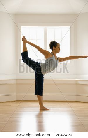 Young woman doing yoga king dancer pose indoors by sunlit window.
