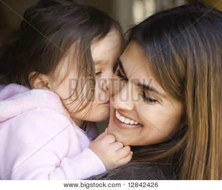 Caucasian mother holding daughter kissing her cheek and smiling.