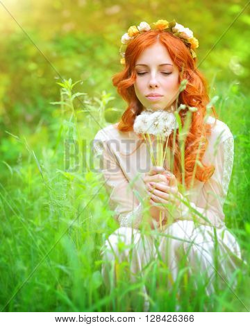 Portrait of a beautiful female wearing floral wreath on red curly hair, enjoying spring garden, holding in hands bouquet of dandelion flowers