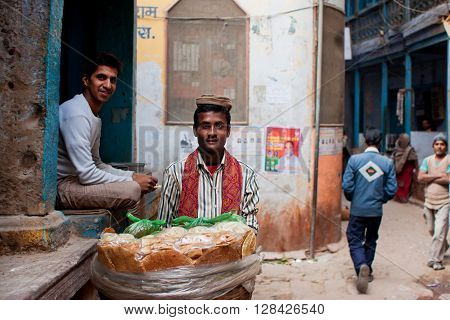 VARANASI, INDIA - JANUARY 1, 2013: Bread trader sells bread on the narrow streets of the oldest city in the world on January 1, 2013 in Varanasi. Varanasi urban agglomeration had a population of 1435113.