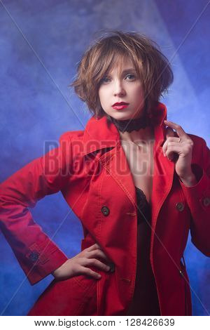 Attractive young woman alluring in sexual lingerie and red coat at smoke background. Beauty, fashion. Concept: seduction, exhibitionism.