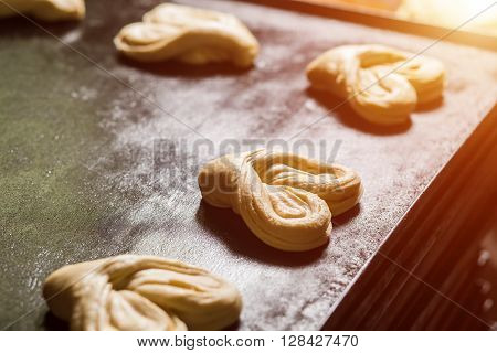 Pastry on baking tray. Heart-shaped baked goods. Delicious and lovely. Quality dough and traditional recipe.