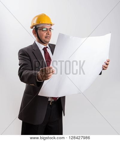 indian businessman holding a blueprint, wearing yellow hard hat, isolated over white background, indian architect with yellow hat and blue print