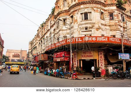 KOLKATA, INDIA - JAN 22, 2016: Old city hotel with people and transport traffic around on January 22, 2013 in Calcutta. Kolkata has a density of 814.80 vehicles per km road length