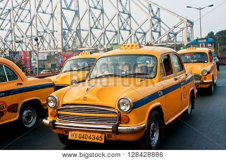 KOLKATA, INDIA - JAN 19, 2016: Yellow taxi cabs stop in traffic jam street with metal bridge background on January 19, 2013 in Kolkata India. Kolkata has a density of 814.80 vehicles per km road length