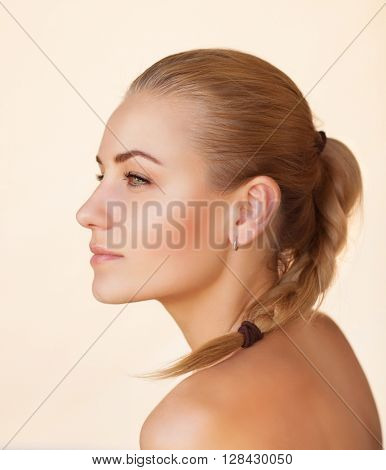Profile portrait of a beautiful sensual woman with braid hairstyle over beige background, gentle natural makeup, natural beauty of a woman face with a healthy skin