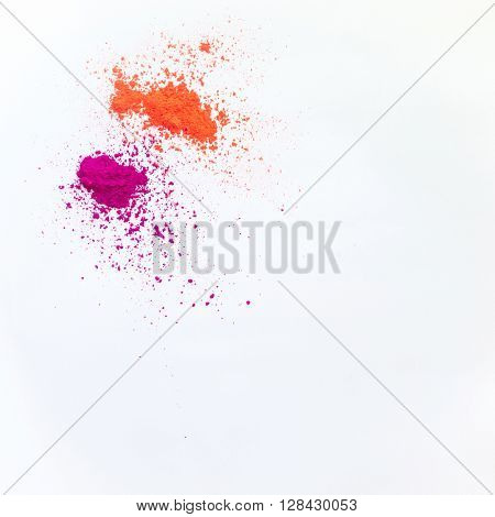 An orange and purple color powder in small quantity  on white background.