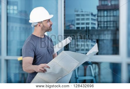 Portrait of an architect builder studying layout plan of the rooms, serious civil engineer working with documents on construction site, building and home renovation, professional foreman at work