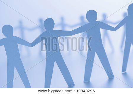 Cutout paper men standing holding hands.
