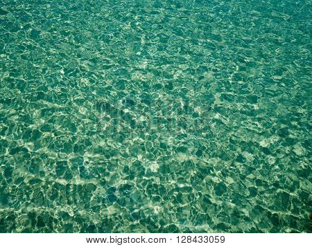 Unique perspective green crystal sea water surface ripple with sun reflection. Water background. Ocean water texture.