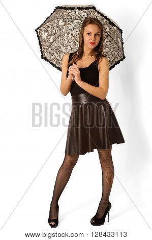 Woman under black umbrella against the white wall.