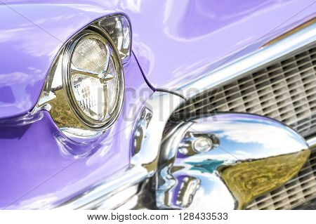 1950s classic car headlight and grille with blurred chrome reflections
