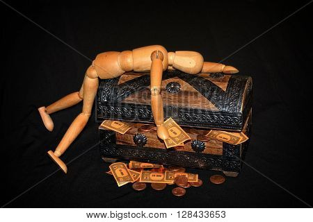 Wooden figure lying on a wooden box with money inside and black background