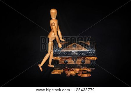 Wooden figure leans left on a wooden box with money against black background