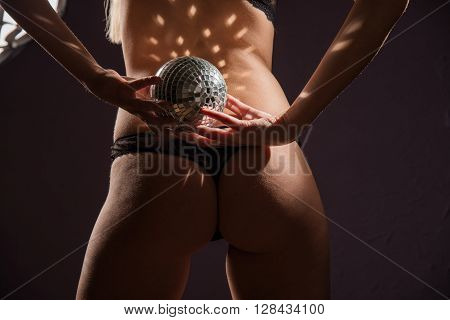 girl is standing back holding mirror ball over black background