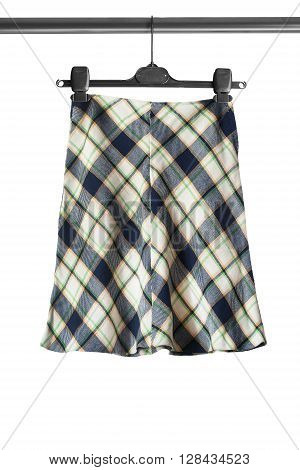 Tartan wool skirt on clothes rack on white background