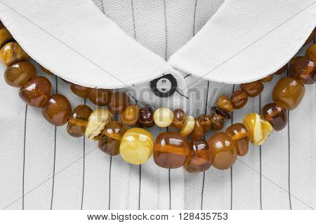 Strings of amber beads on white striped blouse closeup