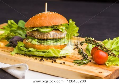 Concept: healthy food. Gourmet homemade burger with garnish and ingredients on the dark background. ** Note: Visible grain at 100%, best at smaller sizes