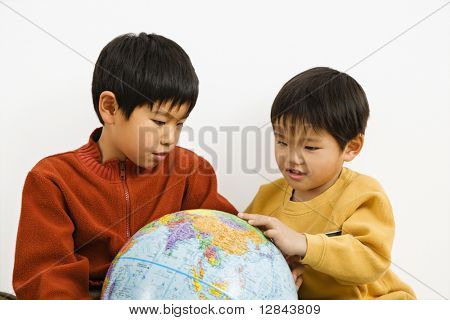 Two Asian boys looking and pointing at world globe