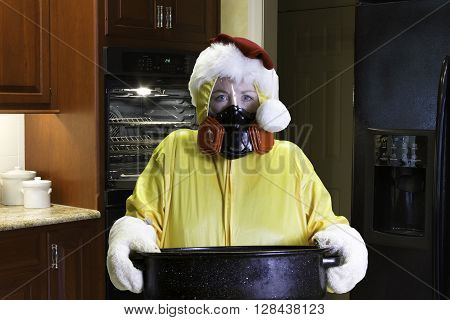 Woman in yellow HazMat suit with respirator wearing a Santa hat holding roasting pan in kitchen.
