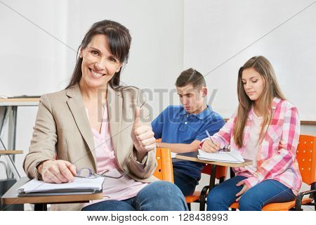 Successful teacher smiling in a high school classroom with her thumb up