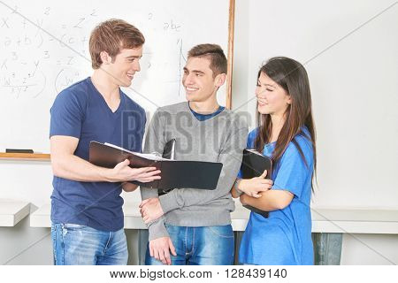Three teenage students present their team work to the class