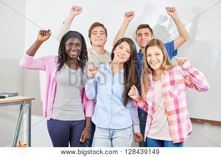 Group of students clench their fists and raise their arms out of joy